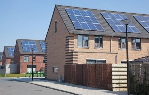 An image of multiple houses fitted with solar panels on the roof